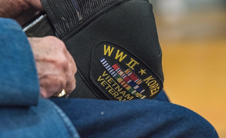 Retired Lt. Col. Clarence Wolgemuth, holds onto his cap during the Veterans Day ceremony where he was recognized for his military service Nov. 9, 2017, at Dover AFB Middle School on Dover AFB, Del. Wolgemuth was stationed at Dover AFB from 1956 to 1964. (U.S. Air Force photo by Roland Balik)