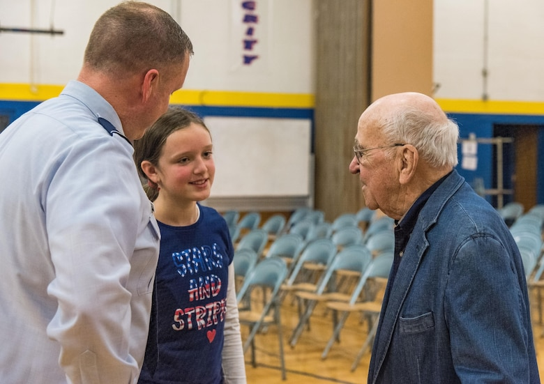 Sixth grade student Emily Goeke, center, daughter of Maj. Robert Goeke, 436th Contracting Squadron commander, left, speaks with retired Lt. Col. Clarence Wolgemuth, right, after the Veterans Day ceremony Nov. 9, 2017, at Dover Air Force Base Middle School on Dover AFB, Del. Wolgemuth, the 2017 DAFBMS Veteran of Honor, met with students and faculty after the ceremony. (U.S. Air Force photo by Roland Balik)