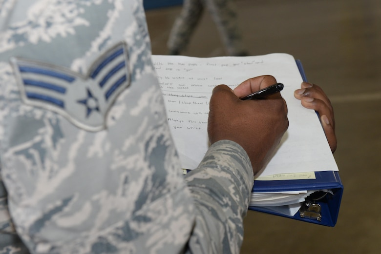 Senior Airman Gerald Mackey, Jr., the Honor Guard flight trainer assigned to the 28th Munitions Squadron, takes notes on the United States Air Force Honor Guard procedures at the Pride Hangar at Ellsworth Air Force Base, S.D., Oct. 26, 2017. The new procedures taught were immediately directed to the honor guard flights that did not participate in the week long course. (U.S. Air Force photo by Airman Nicolas Z. Erwin)