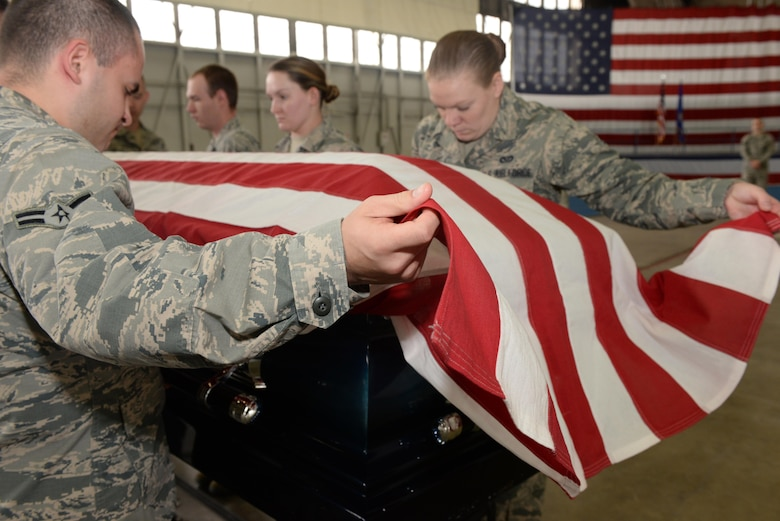 Airmen with the Ellsworth Air Force Base, S.D., Honor Guard lower a casket during a training exercise at the Pride Hangar on base, Oct. 26, 2017. There are three primary retiree sequences: a casket, cremation or vault, each which require different movements and coordination to do properly. (U.S. Air Force photo by Airman Nicolas Z. Erwin)