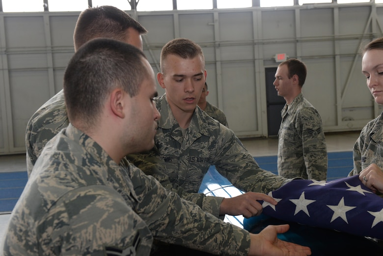 Senior Airman Andrew Zander, a formal training instructor assigned to the United States Air Force Honor Guard, Joint Base Anacostia-Bolling, DC, teaches Airmen with the Ellsworth Air Force Base, S.D., Honor Guard how to properly tuck in the flag during an honors sequence at the Pride Hangar on base, Oct. 26, 2017. The mobile training team had three different members: Senior Airman Andrew Zander was the pallbearer instructor, Senior Airman Anicia Davis was the firing party instructor and Senior Airman Amanda Skidmore was the colors team instructor. (U.S. Air Force photo by Airman Nicolas Z. Erwin)