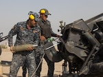 An Iraqi federal police officer loads artillery in support to the fight against the Islamic State of Iraq and Syria near Hawija, Iraq.