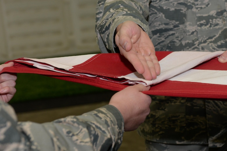Airman 1st Class Joseph Serrano, a material management specialist assigned to the 28th Logistics Readiness Squadron, presents the first fold of a flag during an honor sequence at the Pride Hangar at Ellsworth Air Force Base, S.D., Oct. 26, 2017. The flag folding sequence entails the march-up formation, the casket carry and the flag fold itself which takes place before or after the eulogy is given. (U.S. Air Force photo by Airman Nicolas Z. Erwin)