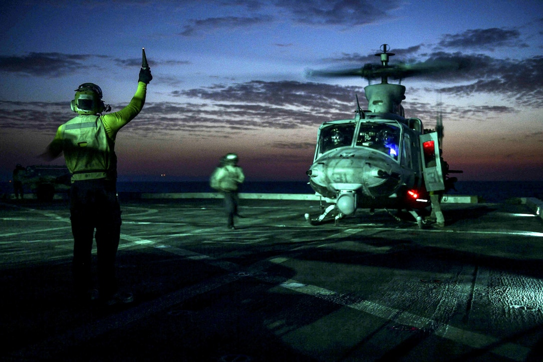 A sailor signals to a helicopter on a flight deck, lit up against a dim blue sky.