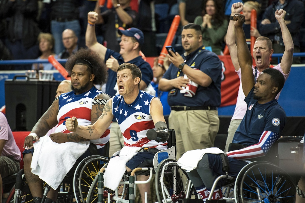 Wheelchair athletes cheer as their basketball team wins.