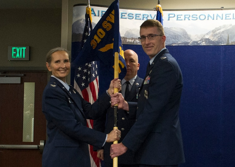 Col. Traci Kueker-Murphy, 310th Space Wing commander, passes the 710th Operations Group guidon to Col. Daniel Bourque during the activation ceremony of the group at Buckley AFB on Saturday, Nov. 4, 2017.