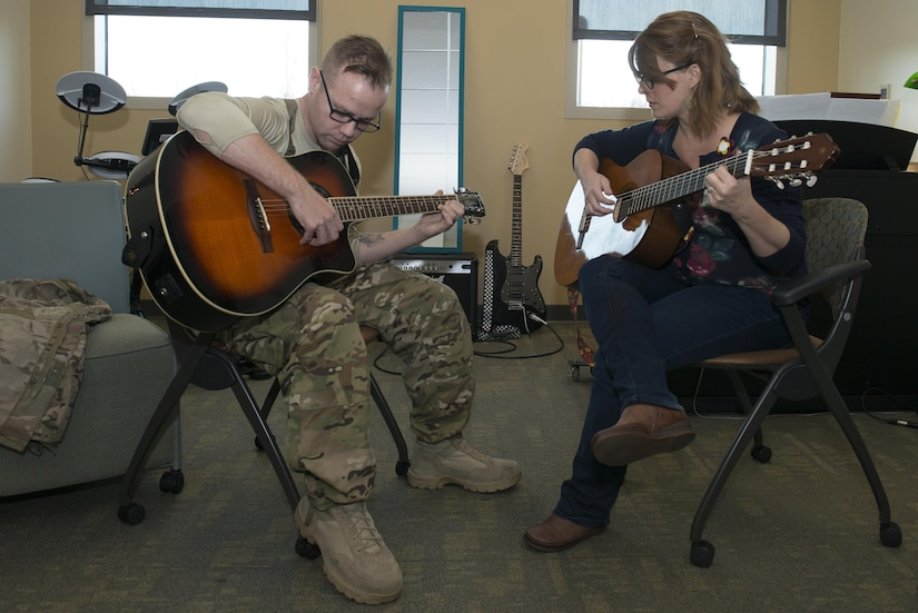 Army Staff Sgt. Sean Young, 2nd Battalion, 377th Parachute Field Artillery Regiment training room noncommissioned officer, strums the guitar during music therapy with Danielle Kalseth, 673d Medical Operations Squadron creative arts therapist/ music therapist, at Joint Base Elmendorf-Richardson, Alaska, Nov. 2, 2017. Music therapy sessions help rehabilitate patients with traumatic brain injury