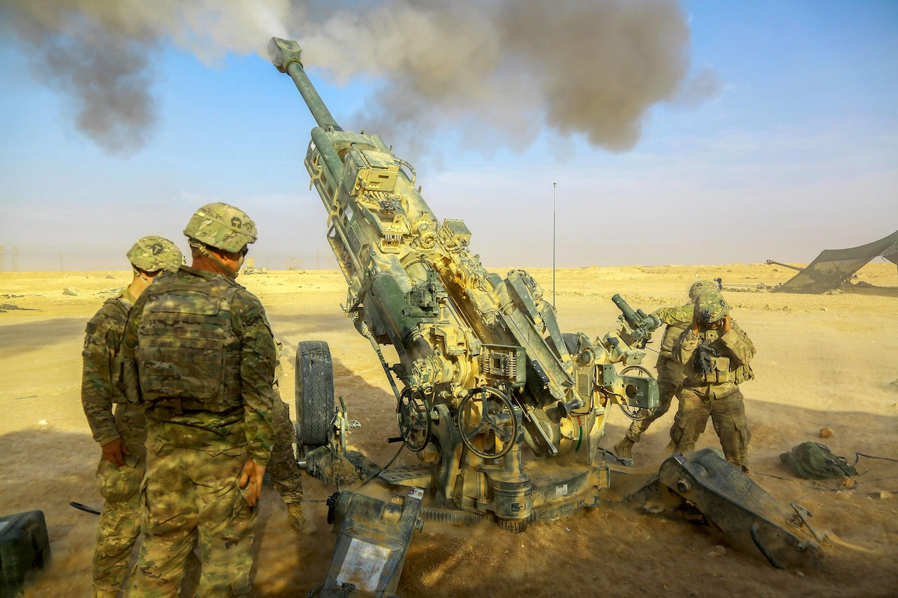 Smoke bursts out of a howitzer as soldiers fire it in desert terrain.