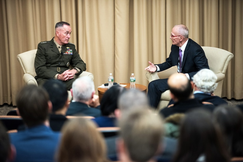 The chairman of the Joint Chiefs of Staff sits on a stage and talks to another person.