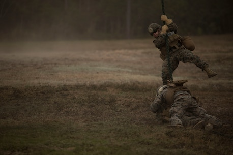 Marines secure a fast rope while a squad member descends during Fast Rope Masters Course 18-1 at Camp Lejeune, N.C., Nov. 9, 2017. Marines fast roped out of an MV-22 Osprey day and night. Newly certified Marines bolster unit readiness because they are now qualified to assist other Marines fast roping into an area of operation. (U.S. Marine Corps photo by Cpl. Victoria Ross)