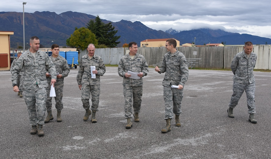 Staff Sgt. Nicholas Cochran (center right), with the 724th Air Mobility Squadron, briefs Maj. gen. Christopher Bence (center), commander, USAF Expeditionary Center and Command Chief Master Sgt. Larry Williams, USAF EC command chief, on the facility upgrade plans for the 724th AMS at Aviano Air Base, Italy, Nov. 6, 2017. Bence and Williams along with the 521st Air Mobility Operations Wing leadership team visited six squadrons of the 521st AMOW at Ramstein AB and Spangdahlem AB, Germany, Aviano AB, Italy and RAF Mildenhall, U.K. (U.S. Air Force photo by Tech. Sgt. Jamie Powell)