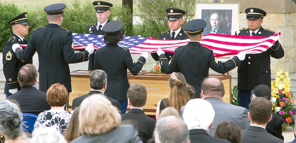 Soldiers from the Military Funeral Honors Caisson Detachment prepare to drape the American flag over the casket bearing the remains of retired Gen. Richard H. Cavazos during Caisson Funeral Honors (Fallen Stars) for Cavazos at the Fort Sam Houston National Cemetery Nov. 14.