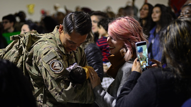 Senior Airman David Ojeda, 31st Maintenance Group crew member, meets his infant child for the first time moments after returning to Aviano Air Base, Italy, Nov. 6, 2017, from a deployment at Bagram Air Field, Afghanistan. Ojeda is one of 380 Airmen and who were deployed from Aviano Air Base to support Operation Freedom's Sentinel. (U.S. Air Force photo by Airman 1st Class Ryan Brooks)