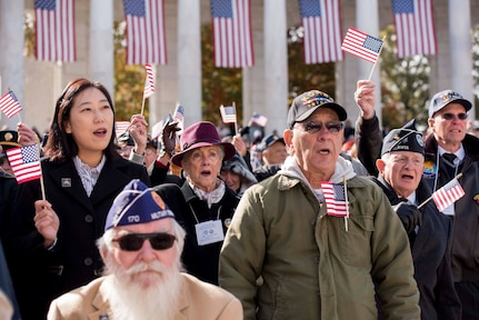 Participants of Veterans Day ceremony wave American flags