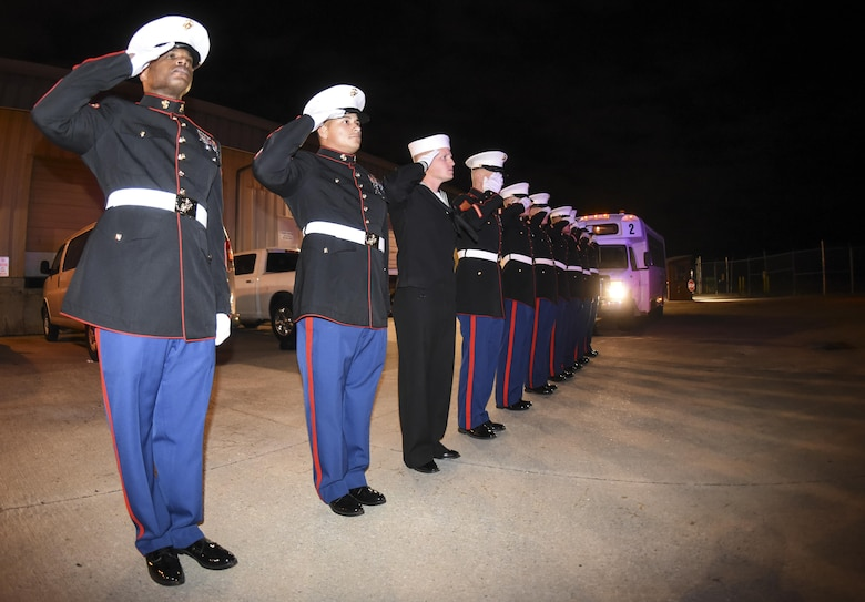 1st Sgt. Kerwin Williams, Marine Corps Honor Guard team leader, left, leads a mixed formation of Marines and a lone sailor in saluting as the remains of Marine Corps Pvt. Vernon Paul Keaton leave the Will Rogers World Airport, Oklahoma City, Oklahoma, Nov. 14, 2017.
