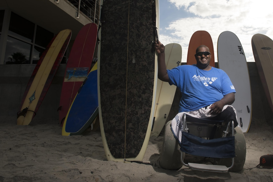 A double amputee veteran sits smiling next to his custom surfboard.