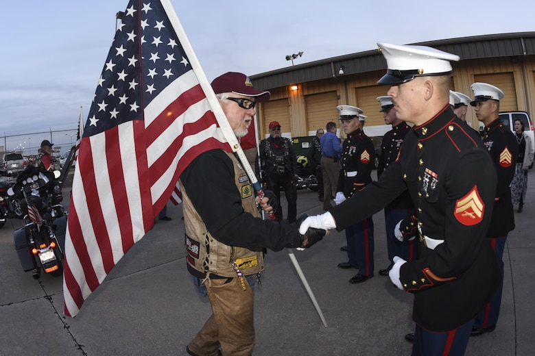 Phil Lutes, an Oklahoma Patriot Rider, carries an American flag while shaking the hand of Marine Corporal David Korn, electro-optical ordnance repair technician, prior to the remains of Marine Corps Pvt. Vernon Paul Keaton arriving in Oklahoma November 14, 2017, Will Rogers World Airport, Oklahoma City, Oklahoma.