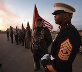 1st Sgt. Kerwin Williams, Marine Corps Honor Guard team leader, right, stands stoically against a colorful Oklahoma sky with members of the Oklahoma Patriot Riders in the background as they await the plane carrying the remains of Marine Corps Pvt. Vernon Paul Keaton November 14, 2017, Will Rogers World Airport, Oklahoma City, Oklahoma.