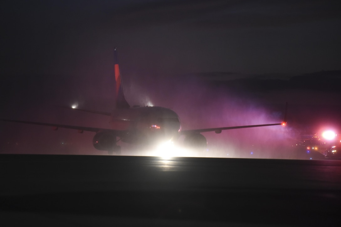 A Delta Airlines Boeing 737 carrying the remains of Marine Corps Pvt. Vernon Paul Keaton is sprayed with water in a symbolic water-cannon salute as the aircraft arrived November 14, 2017, Will Rogers World Airport, Oklahoma City, Oklahoma.