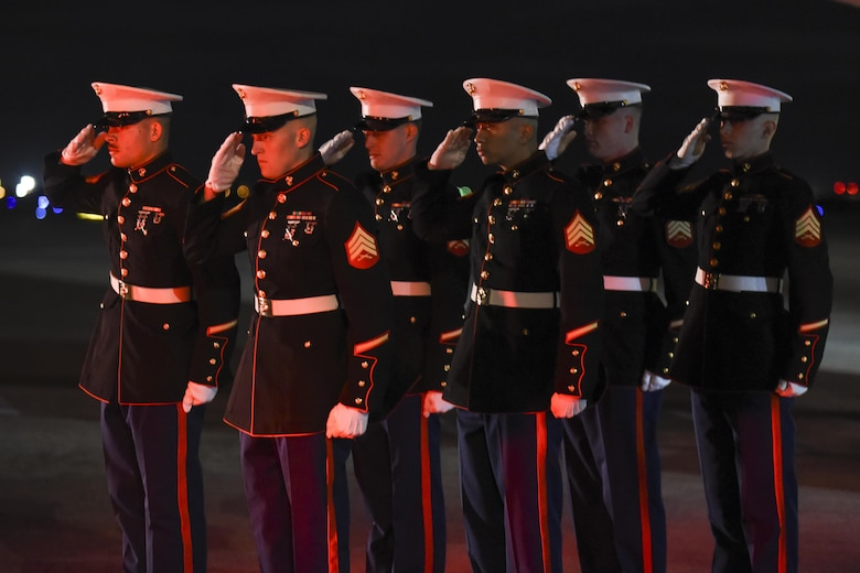 Red light bathes the faces of Marines from Rocket Battery F, 2nd Battalion, 14th Marine Regiment, 4th Marine Division as they salute the hearst carrying the remains of Marine Corps Pvt. Vernon Paul Keaton November 14, 2017, Will Rogers World Airport, Oklahoma City, Oklahoma.