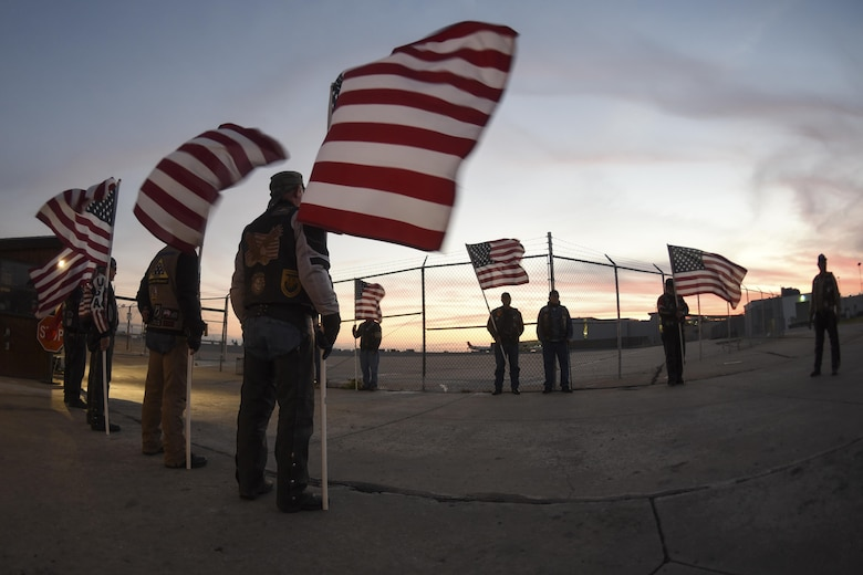 American flags wave against the sunset as members of the Oklahoma Patriot Guard Riders prepare to escort the remains of Marine Corps Pvt. Vernon Paul Keaton November 14, 2017, Will Rogers World Airport, Oklahoma City, Oklahoma.
