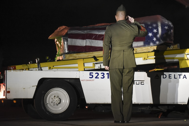 Gunnery Sgt. Nicholas Brundige, Assistant Marine Corps funeral director, Marine Headquarters Barracks, Washington, D.C., salutes the flag draged casket containing the remains of Marine Corps Pvt. Vernon Paul Keaton, as it moves down the conveyor belt after arriving at Will Rogers World Airport November 14, 2017, Oklahoma City, Oklahoma.