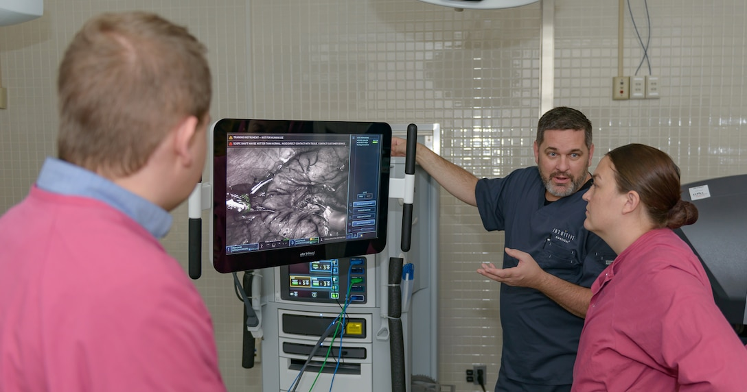Jon Martin, Intuitive Surgical customer trainer, (center), discusses the DiVinci Xi surgical system at the Clinical Research Lab with Dr. Svyatoslav Guznor, 711th Human Performance Wing Airman systems directorate research psychologist, and Capt. Breanna Raney, 711th HPW Airman systems directorate program manager, Air Force Research Lab, Wright-Patterson Air Force Base, Ohio, Nov. 14, 2017, on Keesler Air Force Base, Mississippi. Guznor and Raney visited Keesler to get a better understanding of robotics surgery in the Air Force by touring the InDorse Lab and observing surgeons, nurses, and techs to get basic training on the Da Vinci machine. They also interviewed surgical staff and system trainers on their interactions with the robot and the team dynamics, and collaborated with the lead robotic surgeon about future joint ventures and research collaborations. (U.S. Air Force photo by Andre' Askew)