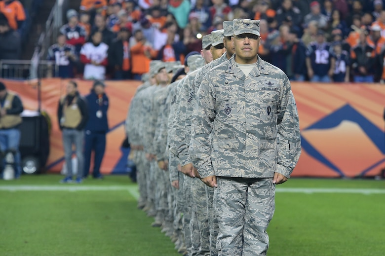 Col. David Miller, Jr., 460th Space Wing commander, leads Buckley Air Force Base members onto the 40-yard line as they prepare for the Salute to Service pre-game ceremony to begin Nov. 12, 2017, at Sports Authority Stadium at Mile High in Denver.