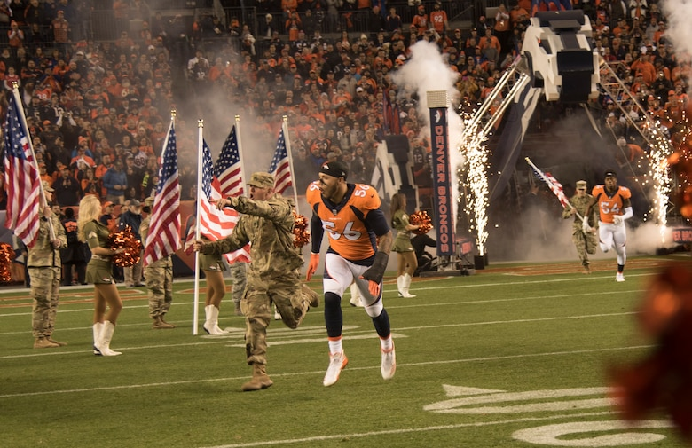 Shane Ray, Denver Broncos outside linebacker, runs out onto the field from the tunnel with a Colorado National Guard member moments before kickoff Nov. 12, 2017, at Sports Authority Stadium at Mile High in Denver.