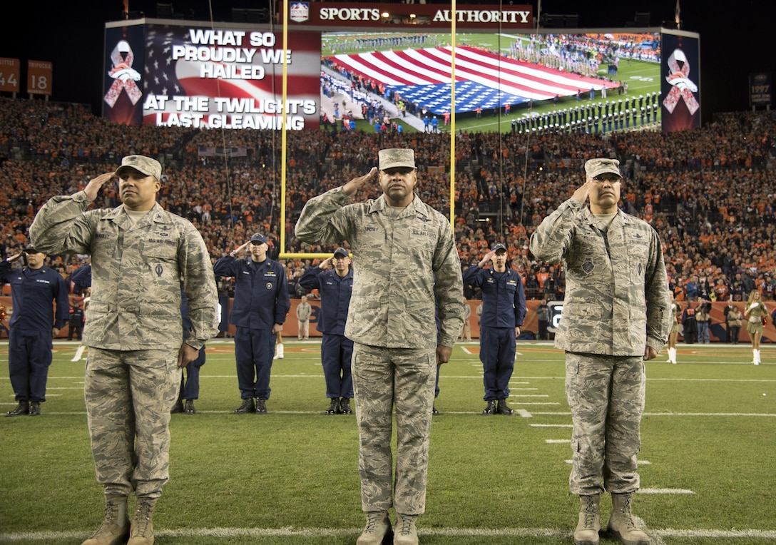 """From left to right: Col. Lorenzo """"Che"""" Bradley, 460th  Operations Group commander, Chief Master Sgt. Rod Lindsey, 460th Space Wing command chief, and Col. David Miller, Jr., 460th Space Wing commander, salute the American flag during the singing of the National Anthem Nov. 12, 2017, at Sports Authority Stadium at Mile High in Denver."""
