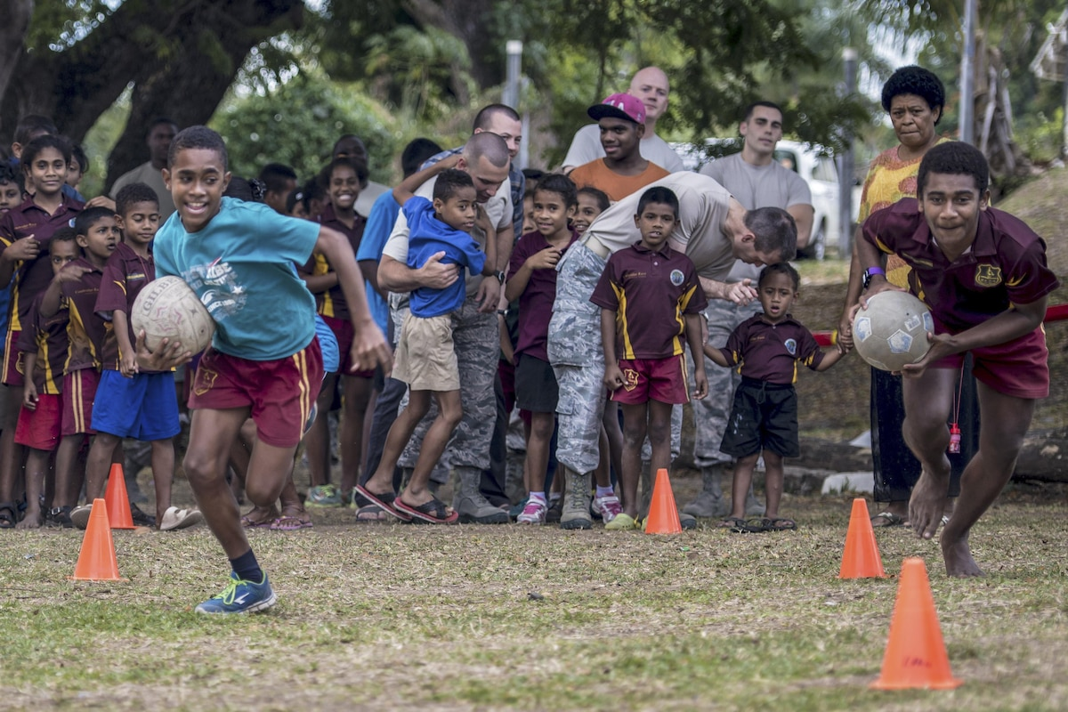 Two Fijian boys hold soccer balls as they race in front of a crowd.