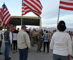 Arizona Patriot Guard Riders stand with American Flags as family and friends welcome home 943rd RQG Airmen.