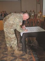 Col. John D. Lawrence, front, Fort Riley garrison commander, and Maj. Gen. Joseph M. Martin, 1st Infantry Division and Fort Riley commander general, sign a proclamation declaring October as Domestic Violence Awareness Month during the Fort Riley Town Hall Oct. 3 at Riley's Conference Center.