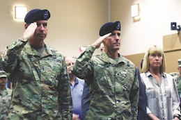 Brig. Gen. Stephen Smith, right, 1st Infantry Division deputy commanding general for support, and Maj. Gen. Joseph Martin, 1st Inf. Div. and Fort Riley commanding general, salute the U.S. flag during the national anthem at a Victory with Honors Ceremony held at the 1st Inf. Div. headquarters building Oct. 3 at Fort Riley. The ceremony was held to welcome Smith and his family to the Fort Riley and the Flint Hills region.