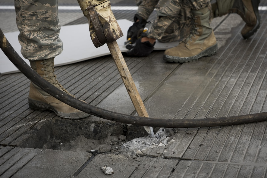 Airman 1st Class Taj Zook, 374th Civil Engineer Squadron pavements and equipment journeyman, operates a jackhammer to remove degraded concrete from the runway, Nov. 15, 2017, at Yokota Air Base, Japan.