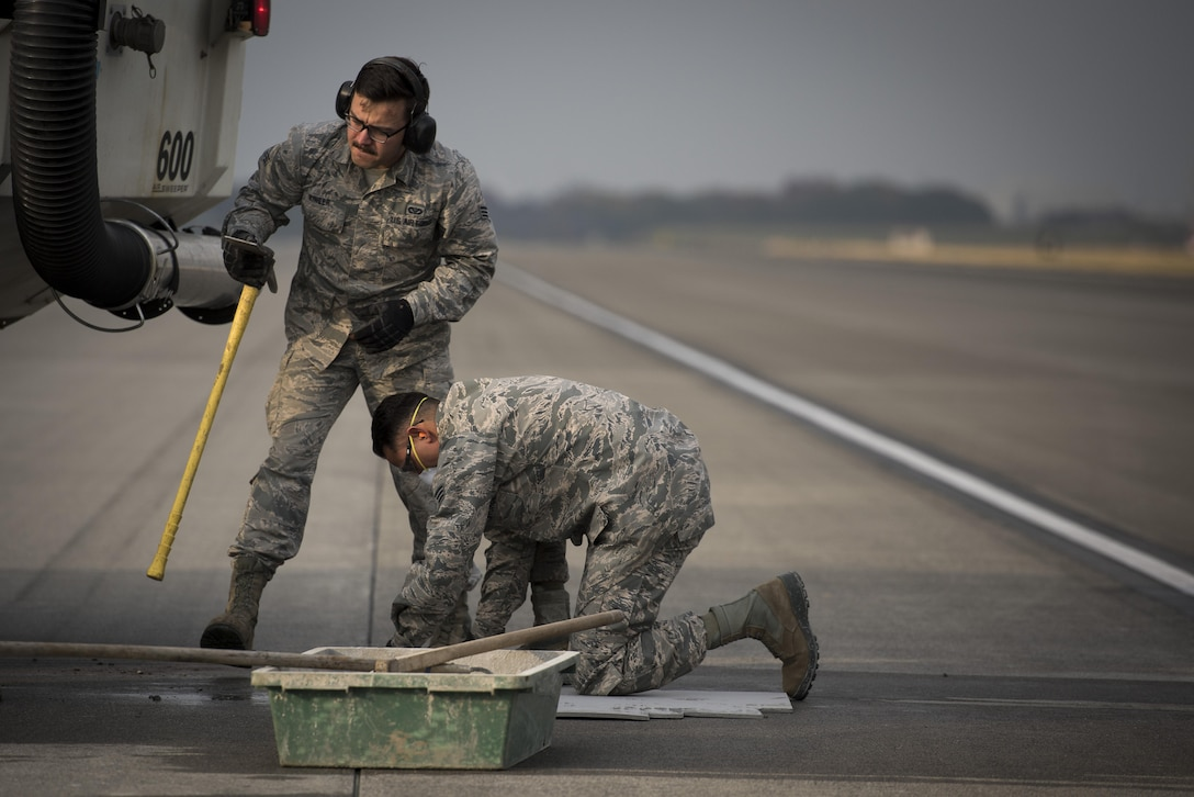 Senior Airman Brendan Kinser, left, and Senior Airman Imran Farooqi, both 374th Civil Engineer Squadron pavements and equipment journeymen, work to repair part of the runway, Nov. 15, 2017, at Yokota Air Base, Japan.