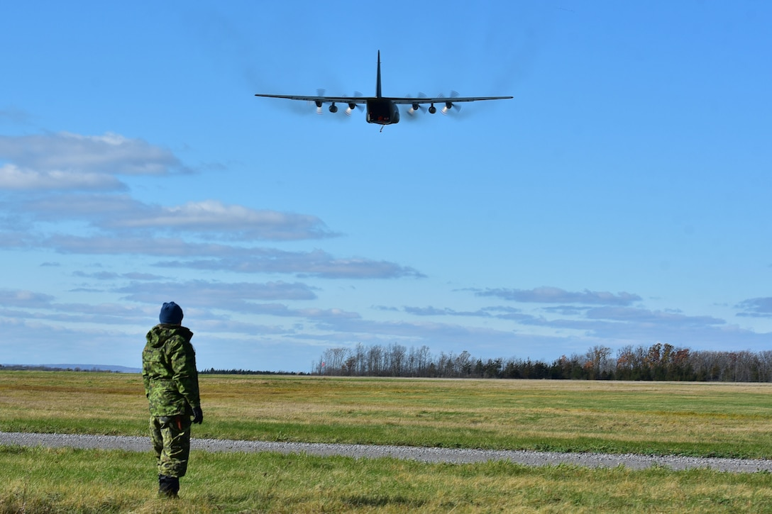 Sergeant Steve Peacock watches a Royal Canadian Air Force C-130H do a low-altitude fly by Nov. 6, 2017, at Canadian Forces base Trenton in Ontario, Canada. The 41st Airlift Squadron, 61st Airlfit Squadron and the 19th Airlfit Wing were invited by the Royal Canadian Air Force to perform exercises in adverse weather conditions. (U.S. Air Force photo by Airman Rhett Isbell)