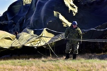 Royal Canadian Air Force Sergeant Steve Peacock, 8 Wing Trenton Combat Aerial delivery support section, works to free a large parachute from trees after it had missed it's target at Canadian Forces base Trenton in Ontario, Canada, Nov. 6, 2017.  The large Container Delivery System had just missed the target and the high winds dragged it into the nearby woods.  (U.S. Air Force photo by SSgt Jeremy McGuffin)
