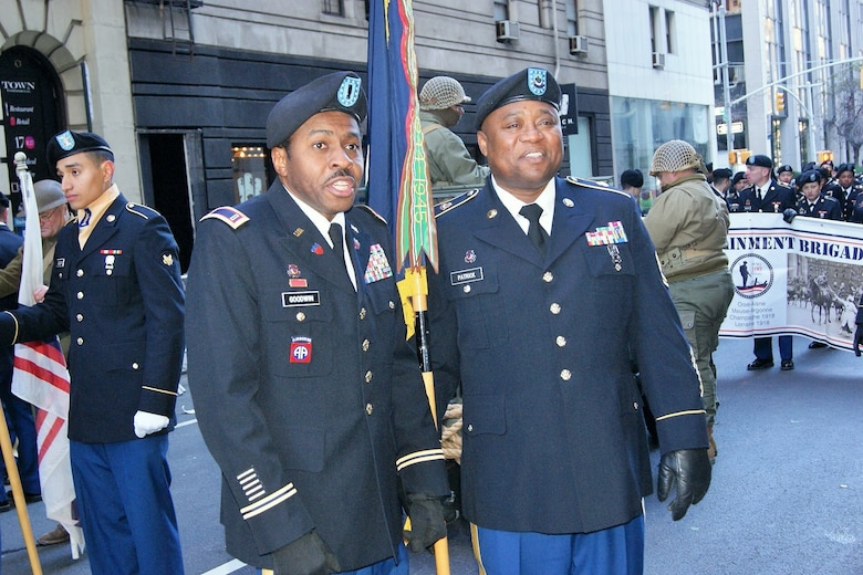 (Left to right) Chief Warrant Officer 3 Eric Goodwin and Sgt. 1st Class Karl Patrick, of the 3rd Brigade Civil Affairs/Military Information Special Operations, 102nd Training Division, 80th Training Command, answer questions in a live-streaming video interview at the New York City Veterans Day Parade Nov. 11, 2017.
