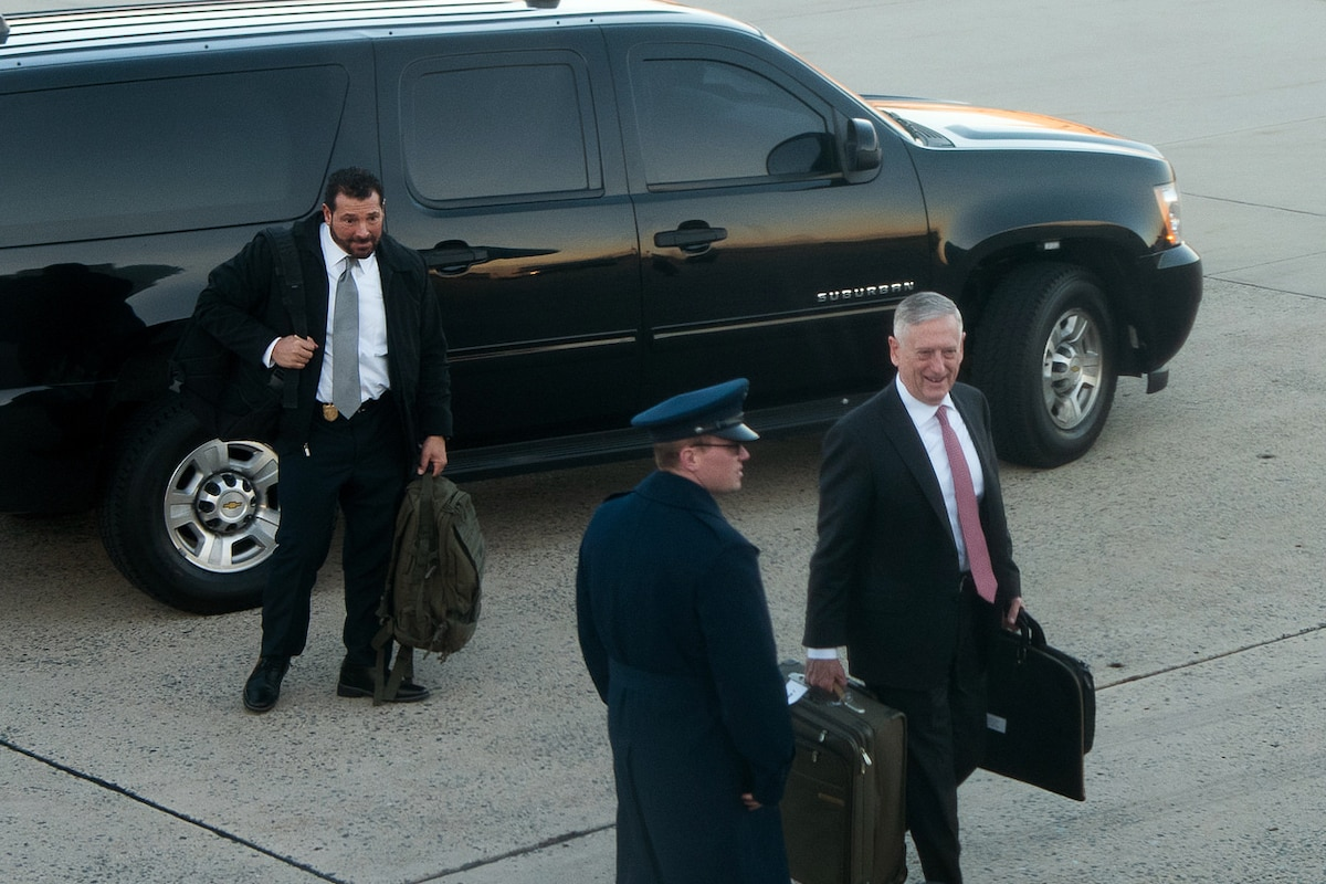 Defense Secretary Jim Mattis walks away from a vehicle with bags.