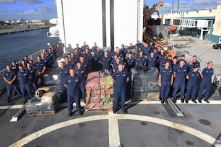 The crew of the Coast Guard Cutter Spencer stands next to approximately 10 tons of seized drugs