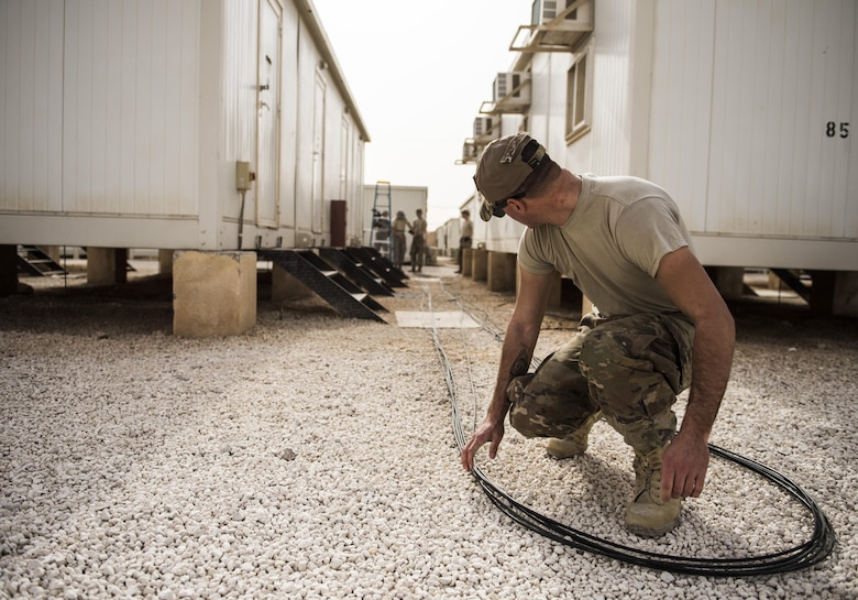 SrA Jacob Ferreira, assigned to the 332nd Expeditionary Communications Squadron, positions copper wire for installation as part of a base-wide wireless internet improvement project Nov. 13, 2017 in Southwest Asia. The 332nd ECS has made rapid improvements to base internet connectivity in recent months, providing deployed service members with a more reliable, flexible connection to home. (U.S. Air Force by Senior Airman Joshua Kleinholz)