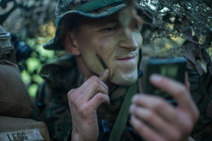 U.S. Marine Corps Lance Cpl. Ryan Savage, a rifleman with 1st Light Armored Reconnaissance Battalion, 1st Marine Division, applies camouflage paint during Exercise Southern Katipo 17 (SK17), at St. Arnaud, New Zealand, Oct. 28, 2017.
