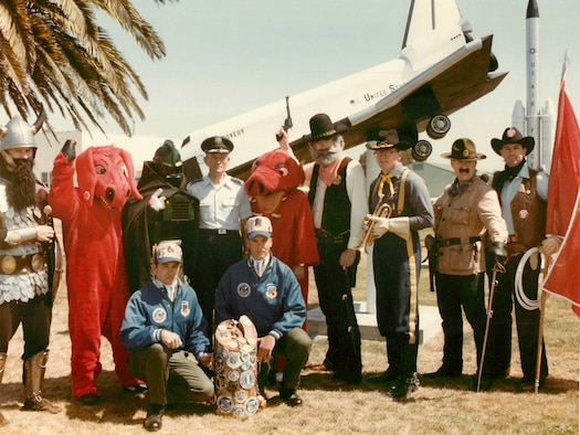 """The 341st Strategic Missile Wing's mascot, the Wrangler, far right, stands with seven other Minuteman and Titan missile wing team mascots around General Bennie L. Davis, commander-in-chief of Strategic Air Command, at the 1985 SAC Missile Combat Competition at Vandenberg Air Force Base, Calif. Malmstrom Air Force Base's team was called """"The Wranglers, """"The First Aces"""" and """"The Ace in the Hole Gang"""" that year. The other mascots represent 321st SMW, Grand Forks AFB, N.D.; 351st SMW, Whiteman AFB, Mo.; 381st SMW, McConnell AFB, Kan.; 308th SMW, Little Rock AFB, Ark.; 44th SMW, Ellsworth AFB, S.D.; 90th SMW, F.E. Warren AFB, Wyo.; and 91st SMW, Minot AFB, N.D. By 1994 the 90th Missile Wing's mascot changed from a cavalry trooper to the Wrangler. (Photo courtesy of 341st MW Historian Office)"""