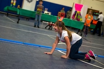 A fashion show participant dressed as a pig crawls down the catwalk during the 23d Civil Engineer Squadron Recycling Science Fair, Nov. 15, 2017, at Moody Air Force Base, Ga. The 23d CES partnered with Moody's Youth Programs for America Recycles Day. The event consisted of a fashion show, where everything was made out of recycled materials. It was designed to help foster more interest in recycling, to increase recycling on base and promote less solid waste to landfills. (U.S. Air Force photo by Airman 1st Class Erick Requadt)