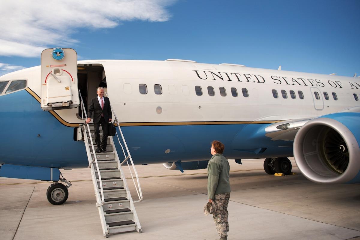 Defense Secretary Jim Mattis walks down the steps off an aircraft.