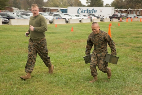 Gunnery Sgt. Jeffrey Sabins, training chief, S3, Headquarters and Service Battalion, U.S. Marine Corps Forces Command follows Sgt. Terry Chung, data network administrator, G6, U.S. Marine Corps Forces Command, as he carries two 30-pound ammo cans as part of the maneuver under fire event of the combat fitness test at the Headquarters and Service Battalion building, at Camp Allen, Norfolk, Va., Nov. 15. Marines were required to carry the ammo cans twice during the event, running more than 150 yards in total. (Official Marine Corps photo by Chris Jones/Released)