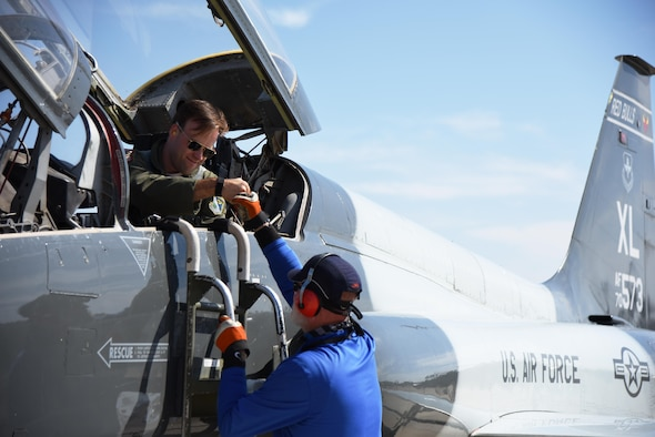 Capt. Robert Ritchie, 87th Flying Training Squadron instructor pilot, fist bumps Rusty Thompson, 47th Maintenance Directorate aircraft attendant, at Laughlin Air Force Base, Texas, Nov. 2, 2017. A team of Laughlin's 87th FTS, also known as the Redbulls, instructor pilots flew four T-38 Talons to Missouri for a flyover of the Kansas versus Baylor football game. (U.S. Air Force photo/Airman 1st Class Anne McCready)