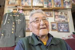 A veteran sits in front of a uniform and photos.