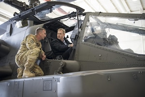 Deputy Defense Secretary Pat Shanahan speaks with a soldier while seated in a helicopter